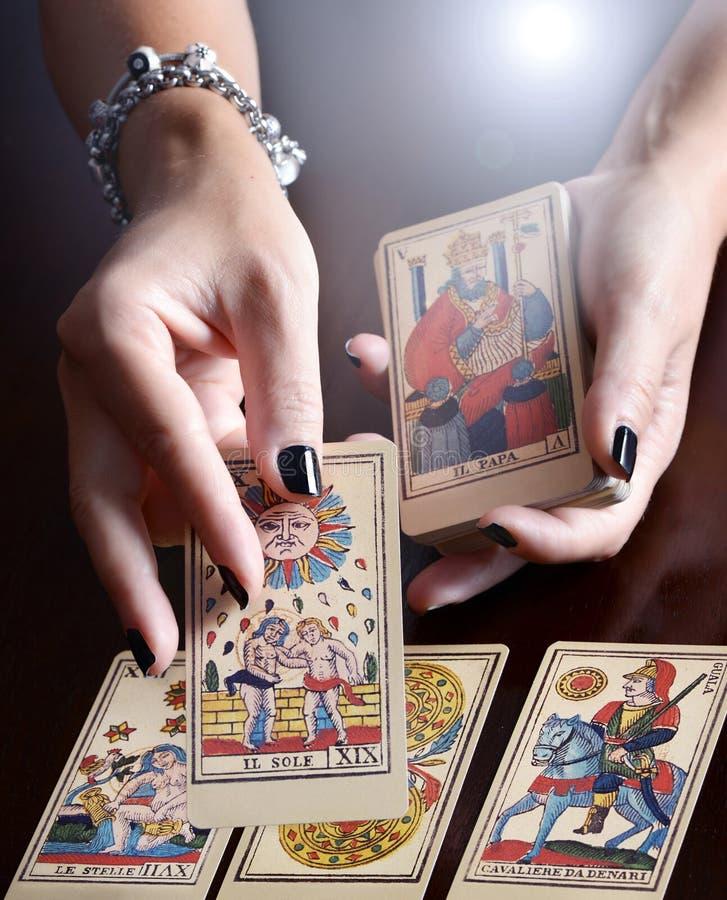 Hände, die Tarock-Karten-Lesung durchführen stockbilder