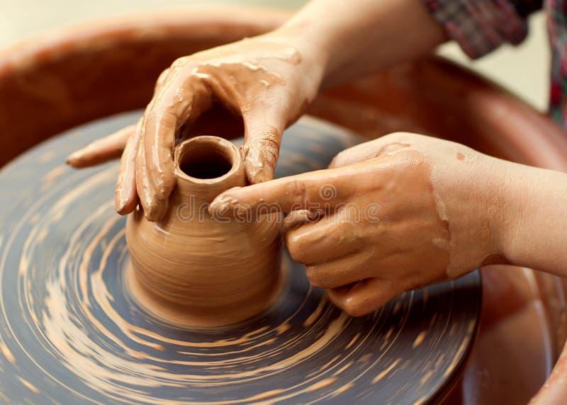 Hände, die an Tonwarenrad arbeiten stockbild