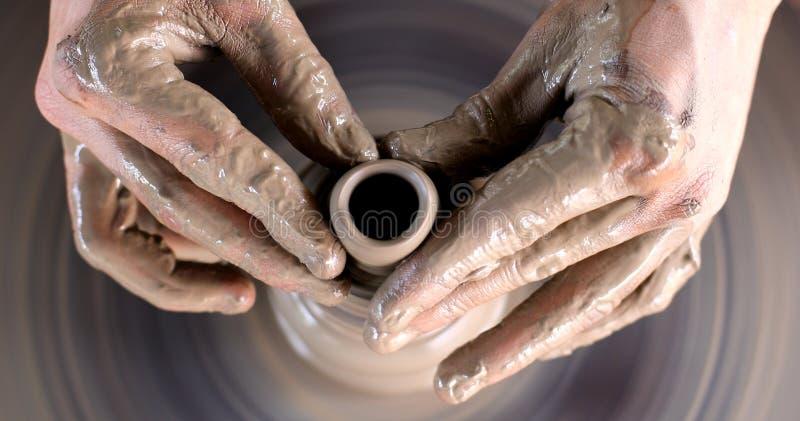Hände, die an Tonwarenrad arbeiten stockfotografie