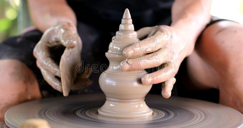 Hände, die an Tonwarenrad arbeiten stockfoto