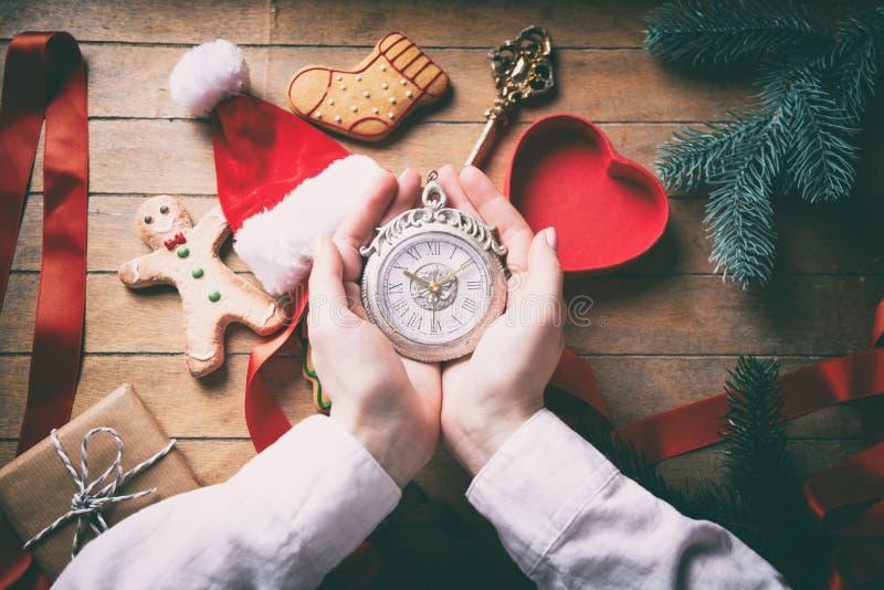 Hände, die Weihnachtenvictorianuhr einwickeln lizenzfreie stockfotografie