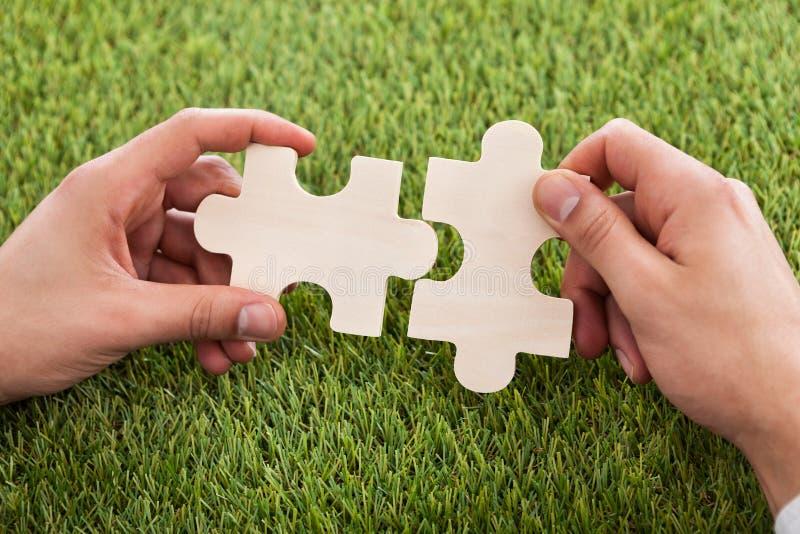 Hände, die zwei Puzzlespielstücke anschließen lizenzfreie stockfotos