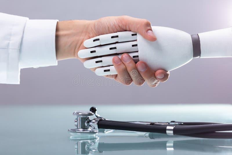 Hände Doktor-And Robot Shaking stockfotos