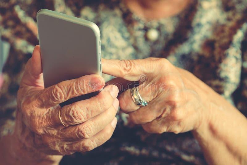 Hände einer älteren Frau, die einen Handy hält stockbild