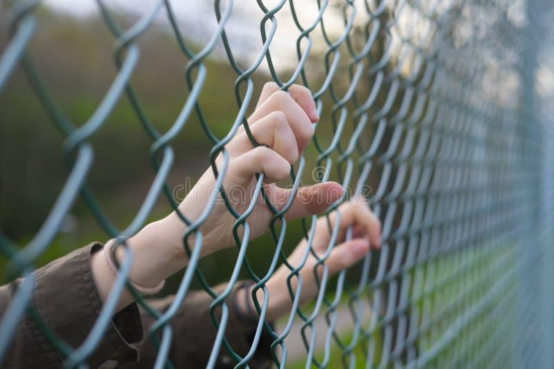 Hände einer Flüchtlingsfrau auf einem Drahtzaun stockbilder