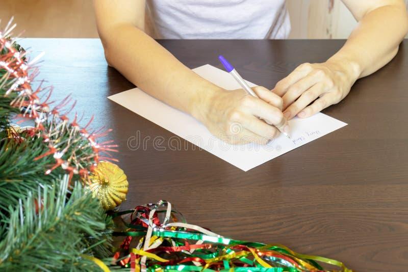 Hände einer Frau, die durch die Tabelle sitzt und Weihnachtswünsche auf eine Karte, Buchstabe schreibt lizenzfreie stockfotos