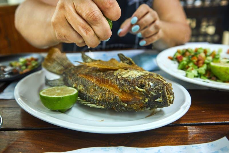 Hände einer Frau, die eine Zitrone hält und gebratene Fische auf einem Platte Sklavenrestaurant gießt stockfotografie