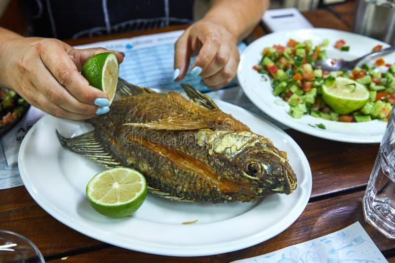 Hände einer Frau, die eine Zitrone hält und gebratene Fische auf einem Platte Sklavenrestaurant gießt stockfotos
