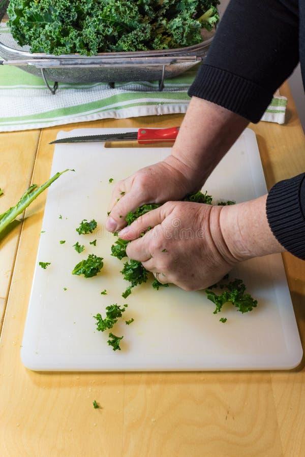 Hände einer Frau, die Kohl zerquetscht und massiert, verlässt, um die starken Fasern aufzugliedern lizenzfreie stockfotografie