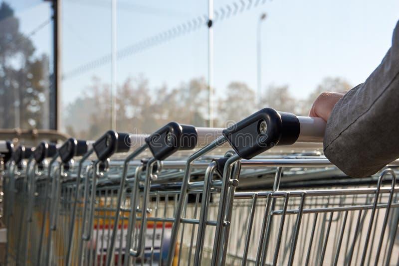 Hände einer jungen Frau, die einen Warenkorb in einem Supermarkt hält stockbilder