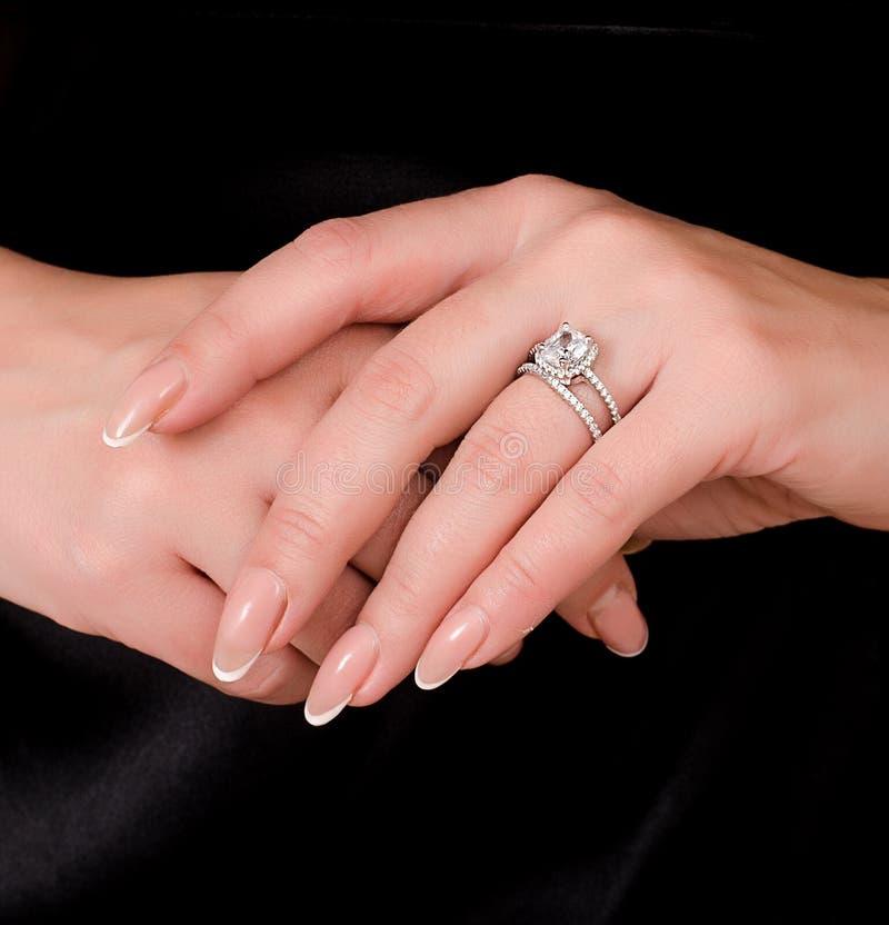 Hände einer jungen Frau mit einem Diamantring auf ihrer Fingernahaufnahme auf einem dunklen Kleiderhintergrund lizenzfreie stockfotografie