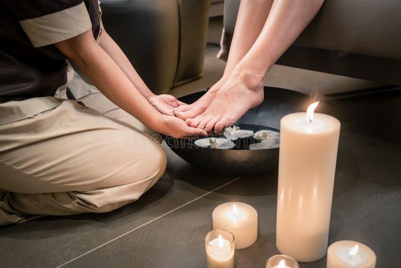 Hände eines asiatischen Therapeuten während der waschenden Behandlung des Fußes lizenzfreies stockfoto