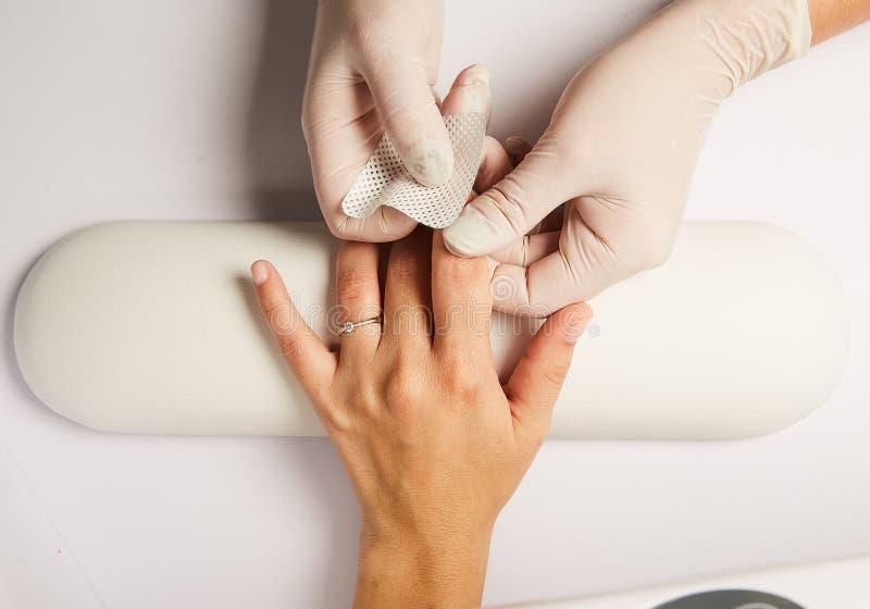 Hände eines Doktors, der klebenden Verband auf kaukasischer Frau des Knies anwendet, lokalisierten weißen Hintergrund stockbilder