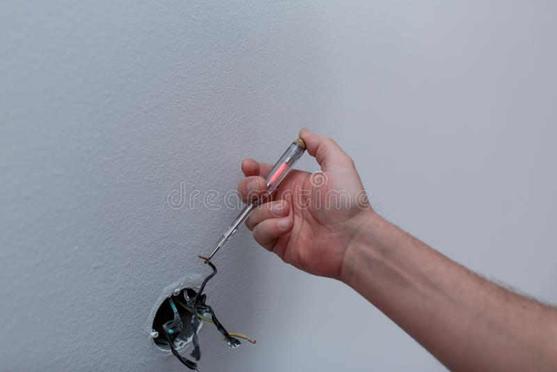 Hände eines Elektrikers, der neues elektrisches Schalter durin installiert stockfoto