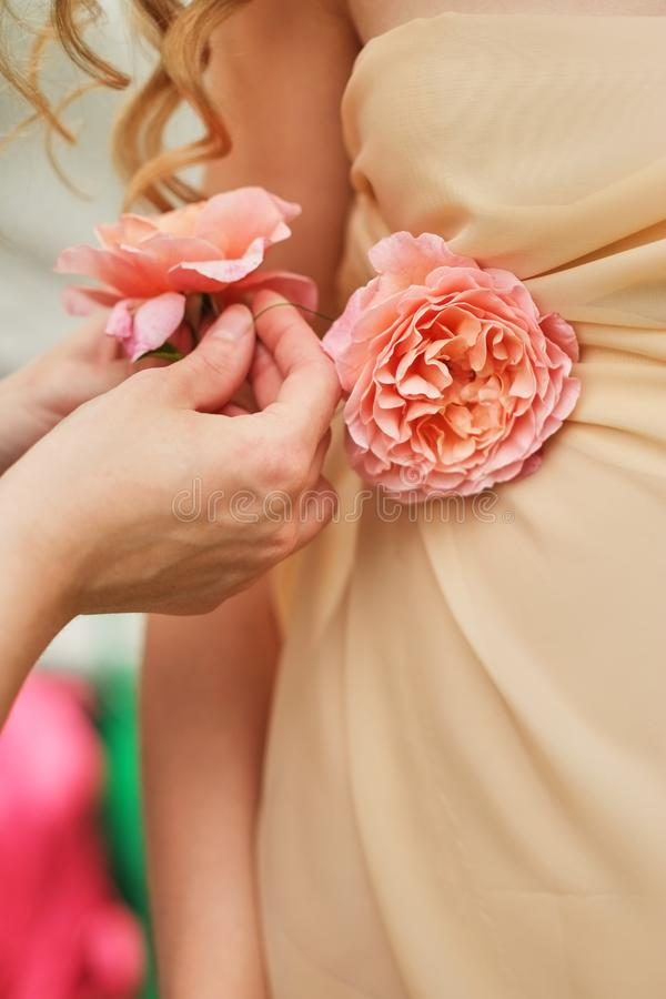 Hände eines jungen Mädchens, das Blumen, Rosen, auf einem Heiratskleid, Nahaufnahme korrigiert lizenzfreie stockfotos