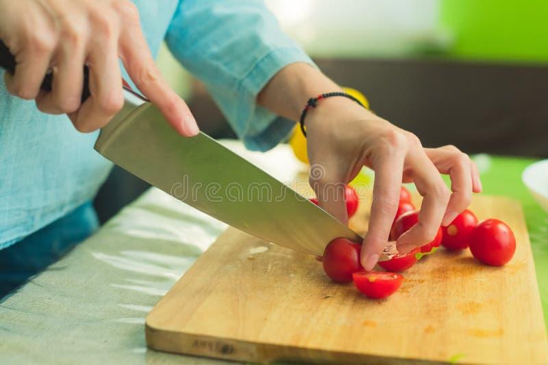 Hände eines jungen Mädchens hacken die Kirschtomaten auf einem hölzernen Schneidebrett auf einer grünen Tabelle in einer Hauptein stockfotografie