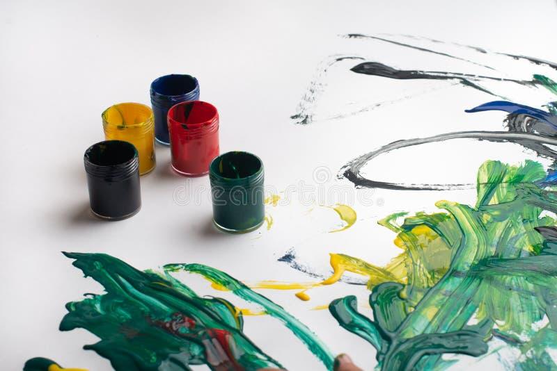Hände eines kleinen Jungen mit Aquarellfarben auf weißem Papierblatt Kleiner Junge mit Pinsel und Farben Zurück zum Schulkonzept lizenzfreie stockbilder