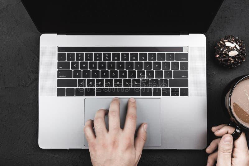 Hände eines Laptopbenutzers, der ihren Kaffee am Frühstück trinkt, Draufsicht stockbilder