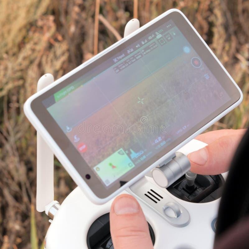 Hände eines Mannes auf dem Steuerknüppelbedienfeld eines unbemannten Luftfahrzeugs Der Landwirt steuert die Brummen und sieht ein lizenzfreie stockfotografie
