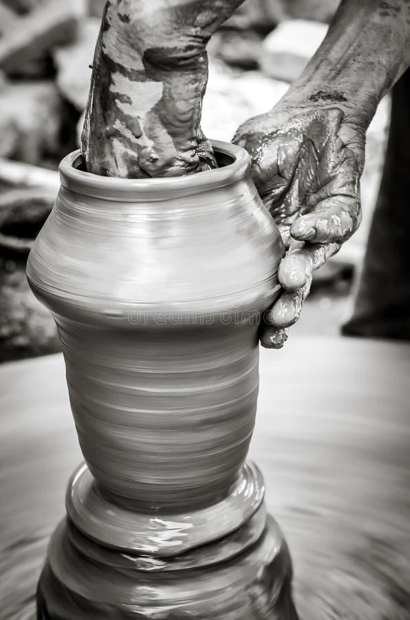 Hände eines Mannes, der Tonwaren auf Rad, einfarbige Weinleseart herstellt stockfotos