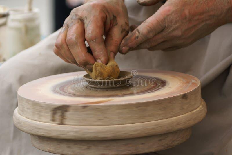 Hände eines Töpfers, ein tönernes Glas auf dem Kreis herstellend lizenzfreies stockfoto