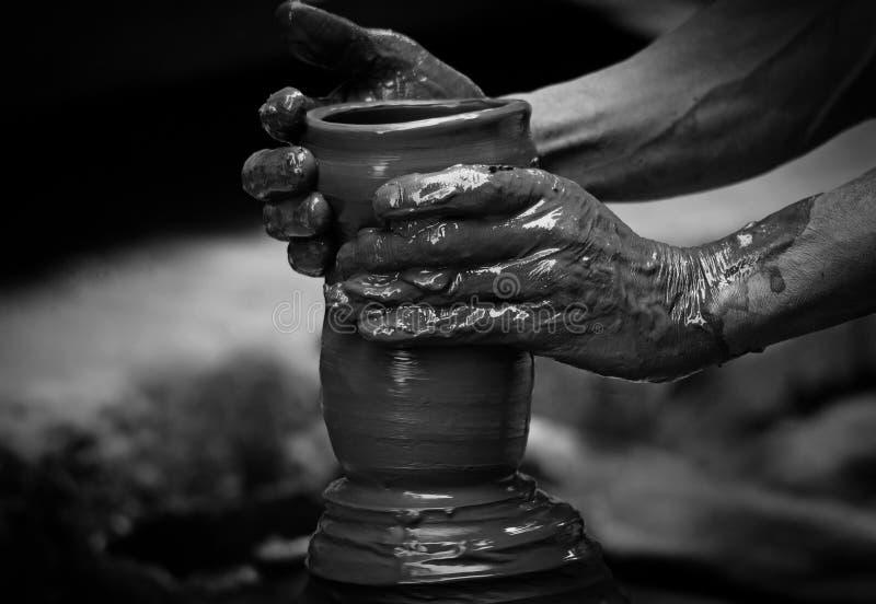 Hände eines Töpfers, ein tönernes Glas herstellend lizenzfreie stockbilder
