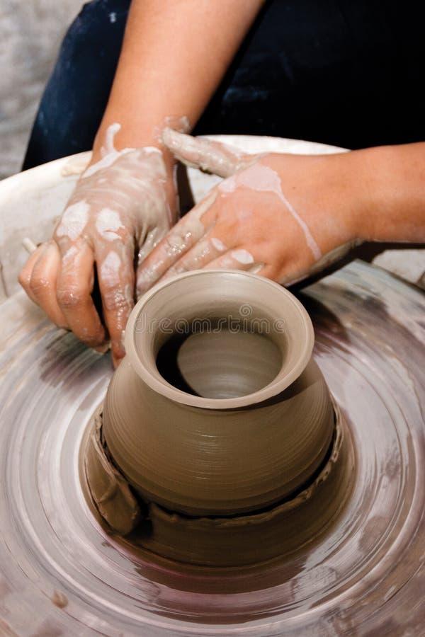 Hände eines weiblichen Töpfers, der ein tönernes Glas herstellt stockbild