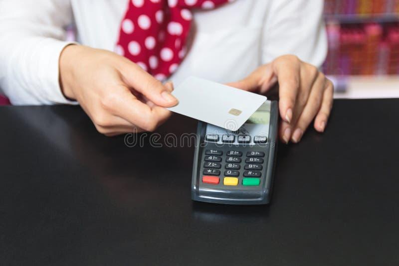 Hände eines weiblichen Verkäufers, der eine Kreditkarte und ein makin hält stockfotografie