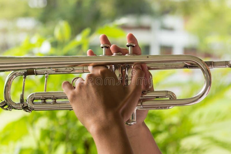 Hände ergreifen die Trompete lizenzfreies stockfoto