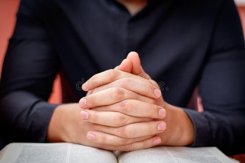 Hände falteten sich im Gebet auf einer heiligen Bibel im Kirchenkonzept für Glauben, spirtuality und Religion lizenzfreies stockfoto