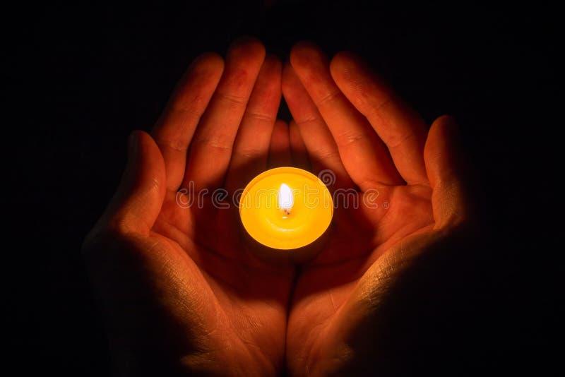 Hände in Form eines Herzens, das eine brennende Kerze auf einem Schwarzen hält lizenzfreie stockfotos