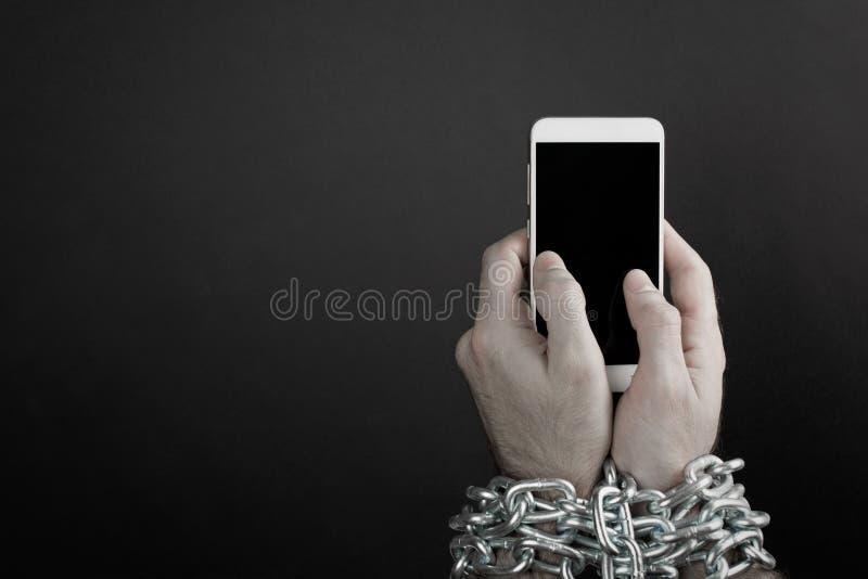 Hände gebunden mit metallischer Kette am Smartphone lizenzfreie stockfotos