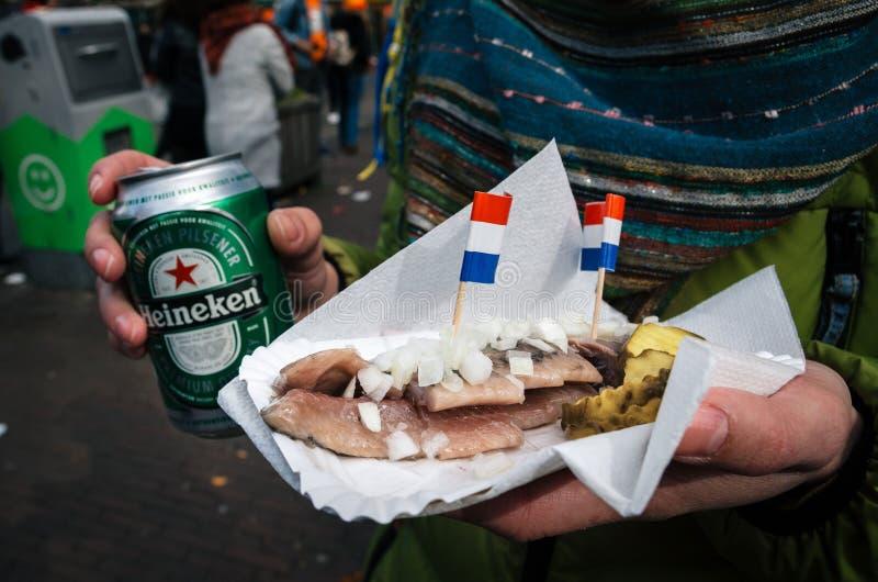 Hände halten ein Bier Heineken und eine niederländische Zartheit von Heringen mit Essiggurken und Zwiebeln stockbild