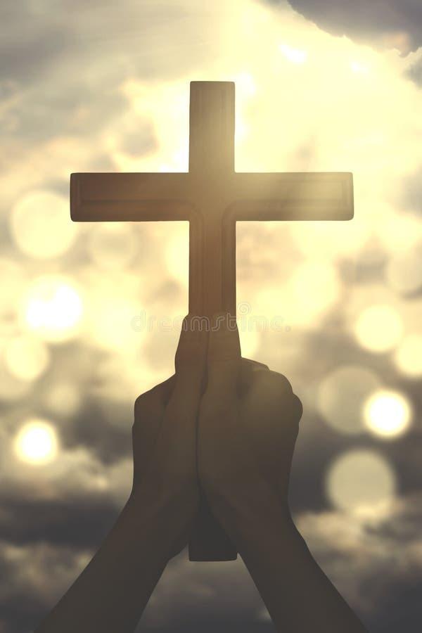 Hände halten ein Kreuz mit Sonnenstrahl lizenzfreies stockbild