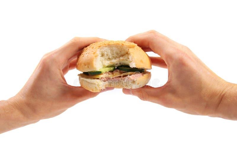 Hände halten einen Burger an stockbilder