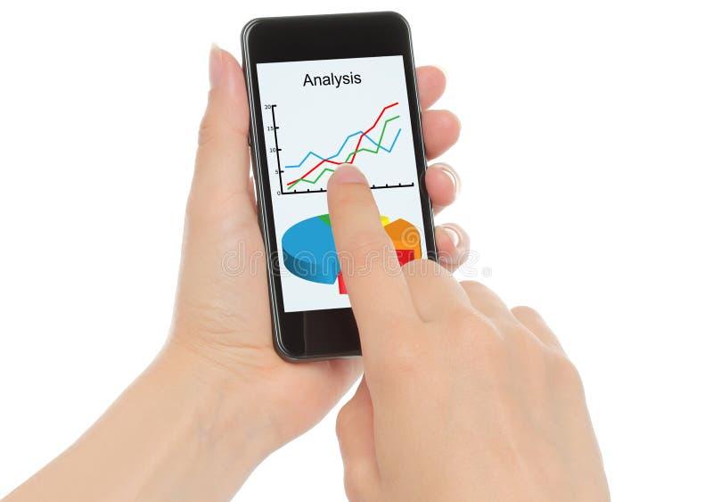 Hände halten intelligentes Telefon mit Diagrammen stockfoto