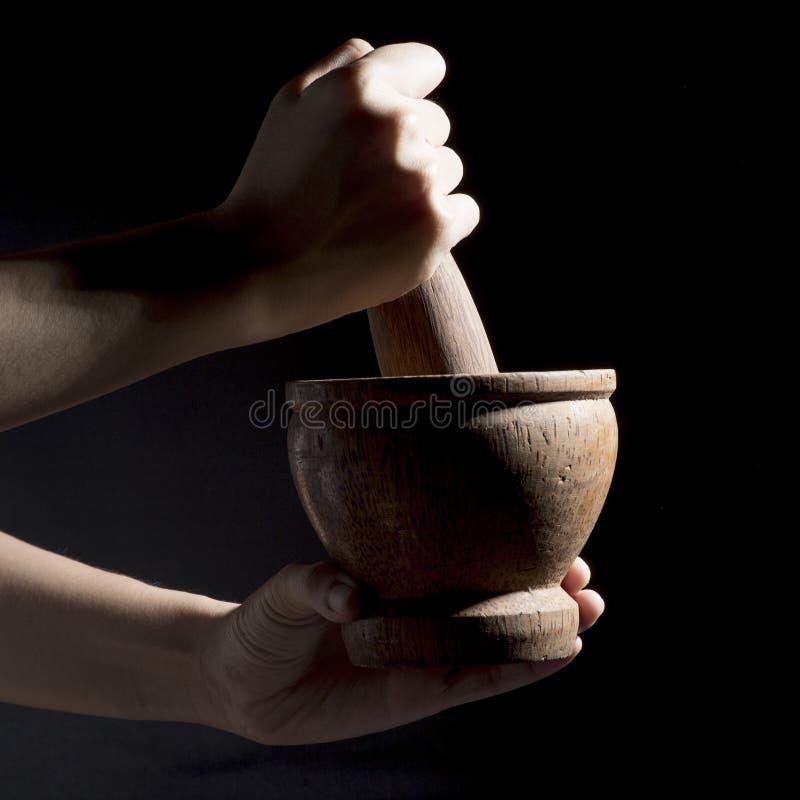 Hände halten Stampfe und zerquetschen zum hölzernen Mörser stockbild