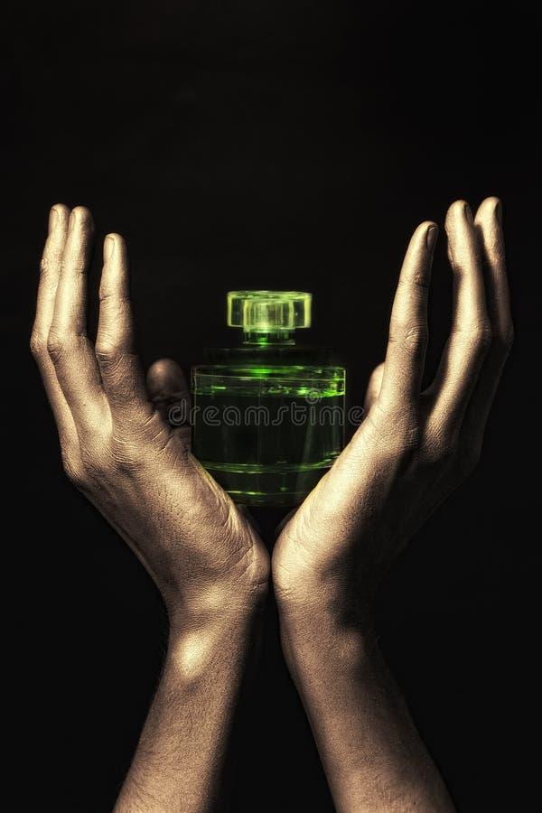 Hände im goldenen Lack, der grüne Flasche anhält lizenzfreie stockfotografie