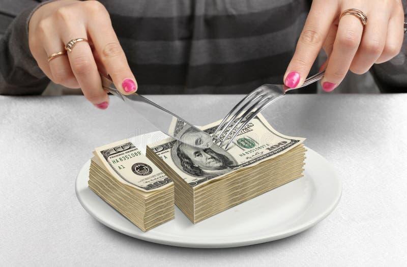 Hände kürzten Geld auf Platte, verringern Kapitalskonzept stockbilder