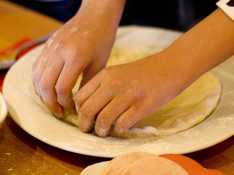 Hände machen Pizza, Arbeit mit Teig auf einer weißen Platte stockbilder