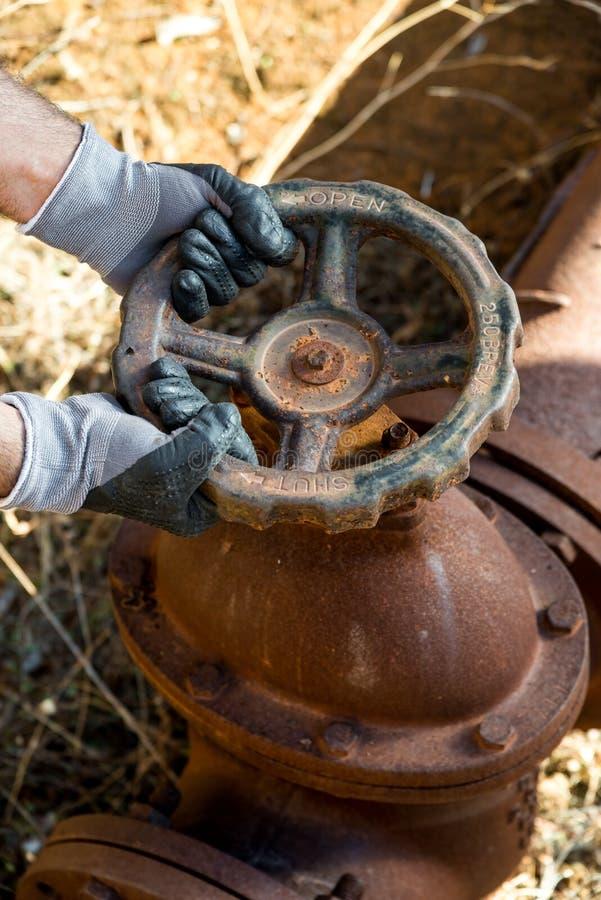 Hände mit den Arbeitshandschuhen, die einen Schutzhelm, einen Schlüssel und ein Rot halten, befestigen Rohrschellen lizenzfreies stockfoto