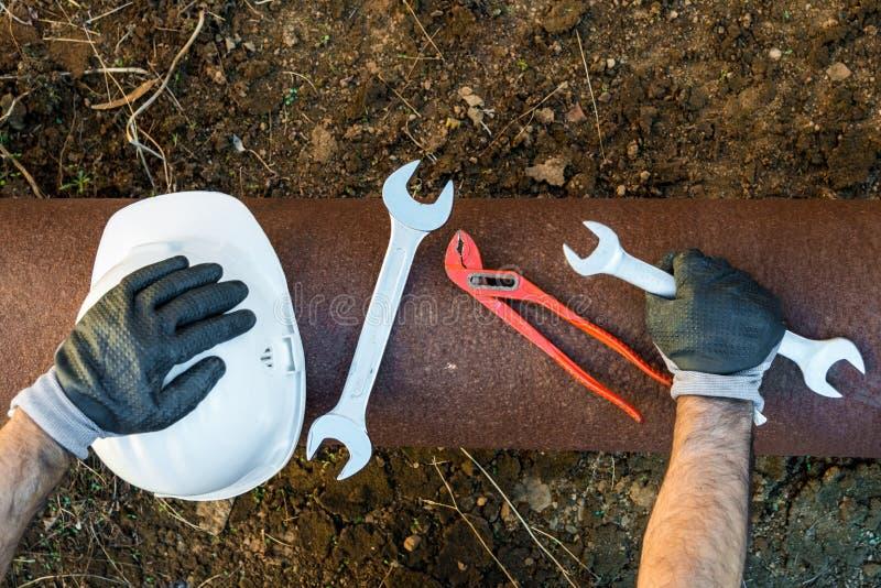 Hände mit den Arbeitshandschuhen, die einen Schutzhelm, einen Schlüssel und ein Rot halten, befestigen Rohrschellen stockfotografie