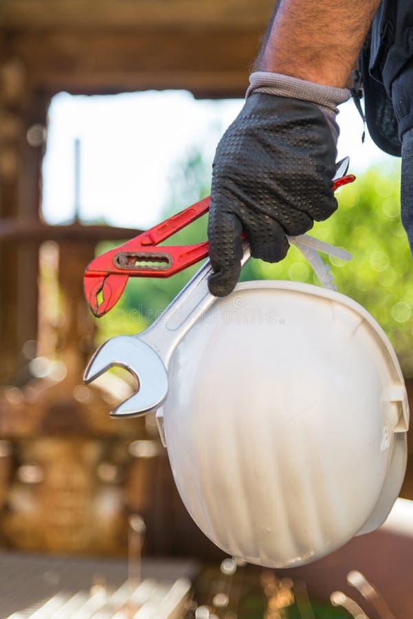 Hände mit den Arbeitshandschuhen, die einen Schutzhelm, einen Schlüssel und ein Rot halten, befestigen Rohrschellen lizenzfreie stockfotos