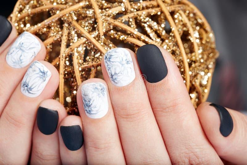 Hände mit den kurzen manikürten Nägeln gefärbt mit Schwarzweiss-Nagellack stockbilder