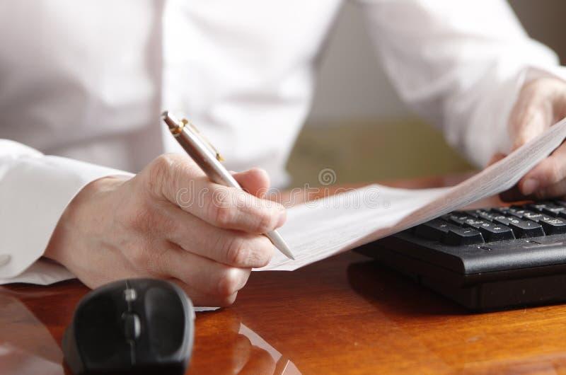 Hände mit Dokument und Stift auf einer Computertastatur stockfoto