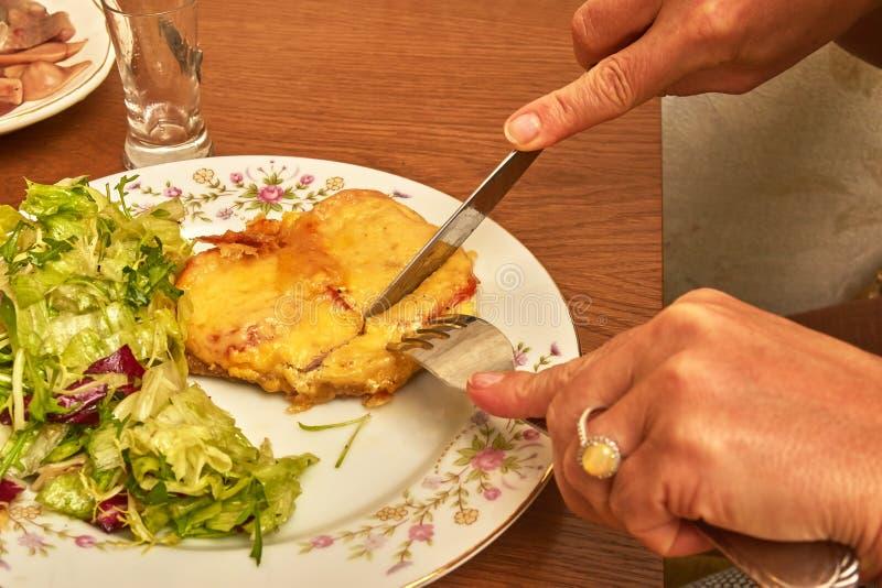 Hände mit einem Messer und einer Gabel schnitten das Fleisch auf einer Platte lizenzfreie stockfotografie