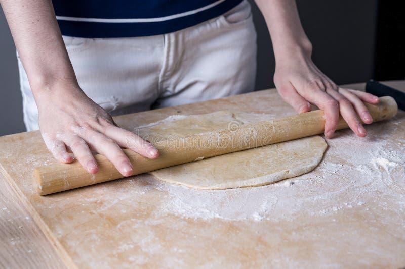 Hände mit einem Nudelholz stellen den Teig auf einem braunen Holztisch, Bullauge, Vorderansicht bereit stockfotos