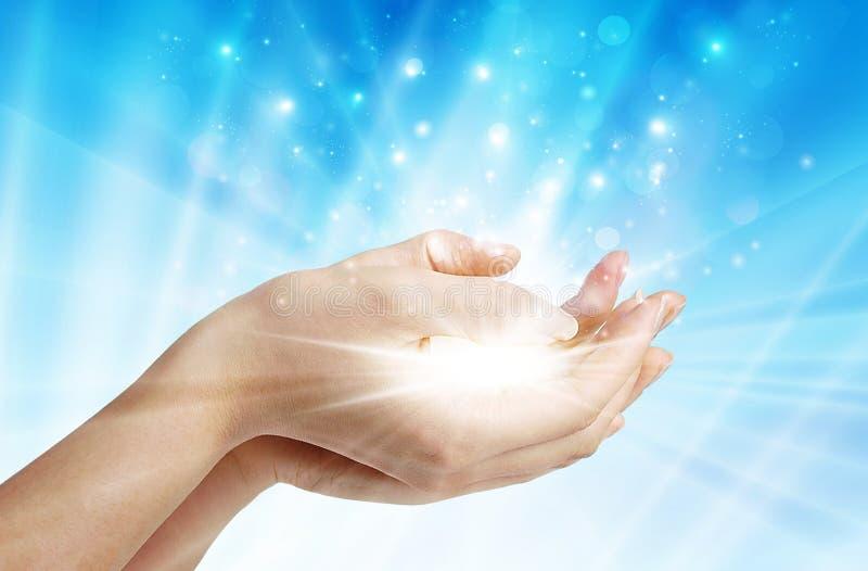 Hände mit Funken der Hoffnung, das Licht des Glaubenhintergrundes lizenzfreie stockfotos
