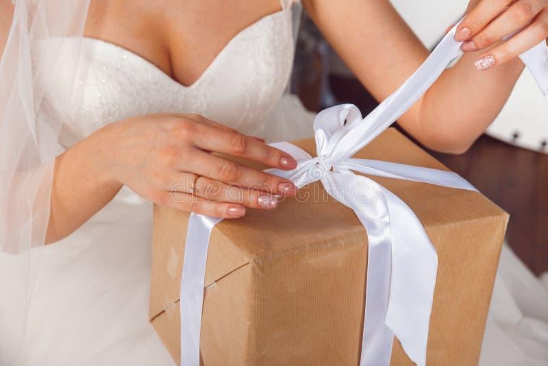 Hände mit Geschenkbox auf der Hochzeitsfeier Studioporträts der schönen Braut mit Geschenk Braut, die Geschenk hält Weihnachten stockfotografie