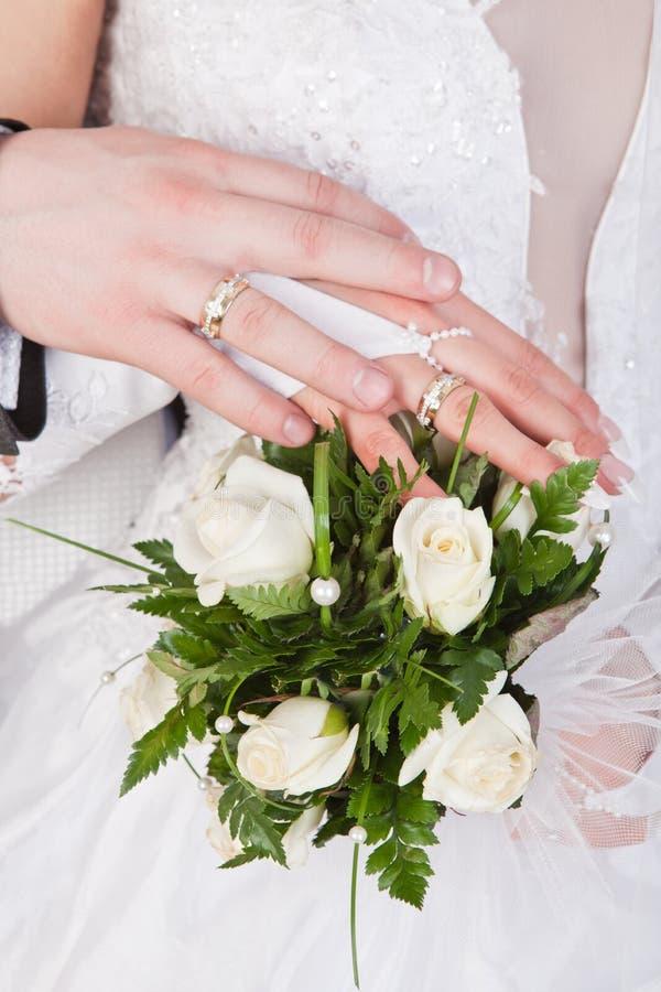 Hände mit Ringen und Hochzeitsblumenstrauß lizenzfreie stockbilder